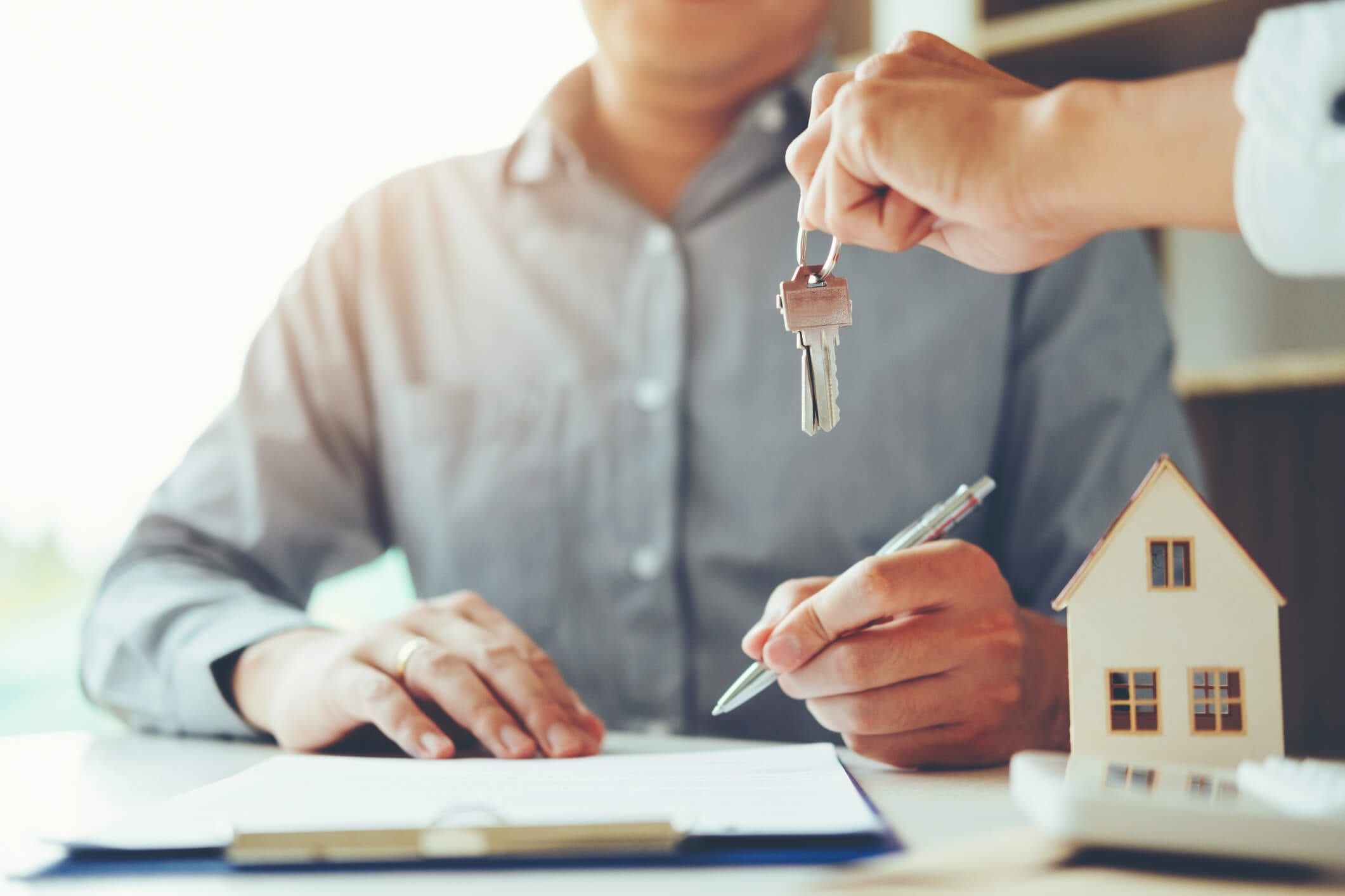 Estate Agent handing over the keys to the new homeowner that is signing housing documentation