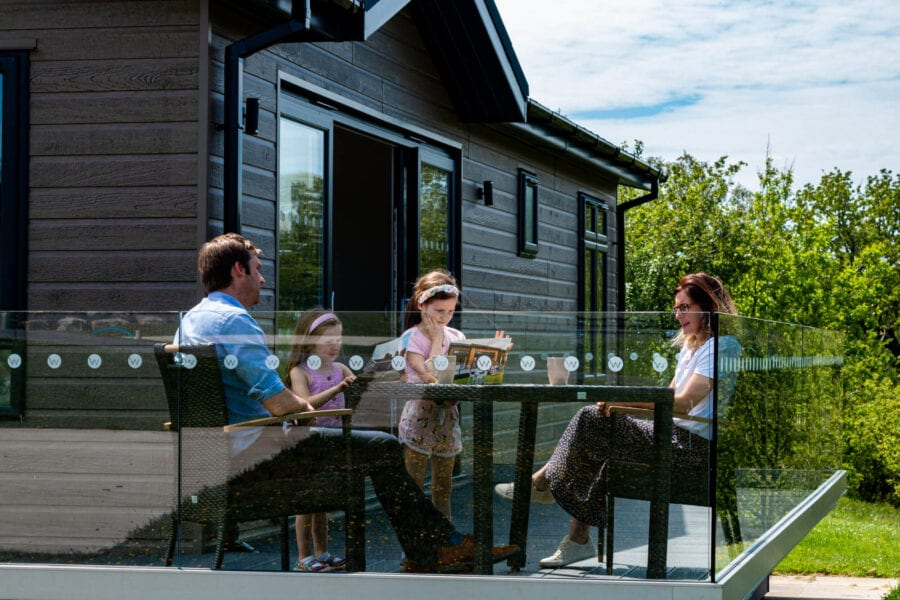 Family looking at a Wenningdale Escapes brochure while sat outside on the veranda on outdoor furniture at Wenningdale Escapes